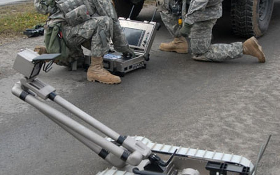Pvt. Blake Tyndall, 19, of Richlands, N.C., left, and 1st Lt. Elvis Gonzalez, 28, of Houston prepare to deploy a Pacbot to deal with a mock roadside bomb.