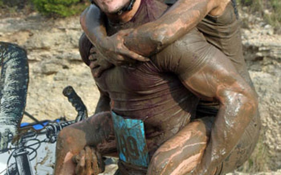 """Capt. Hollie Diesselhorst, 909th Aerial Refueling Squadron, and Capt. Tom Hunt, 67th Fighter Squadron celebrate after finishing a """"muddy buddy"""" race together. Muddy buddy is a six to seven mile foot and bike race."""