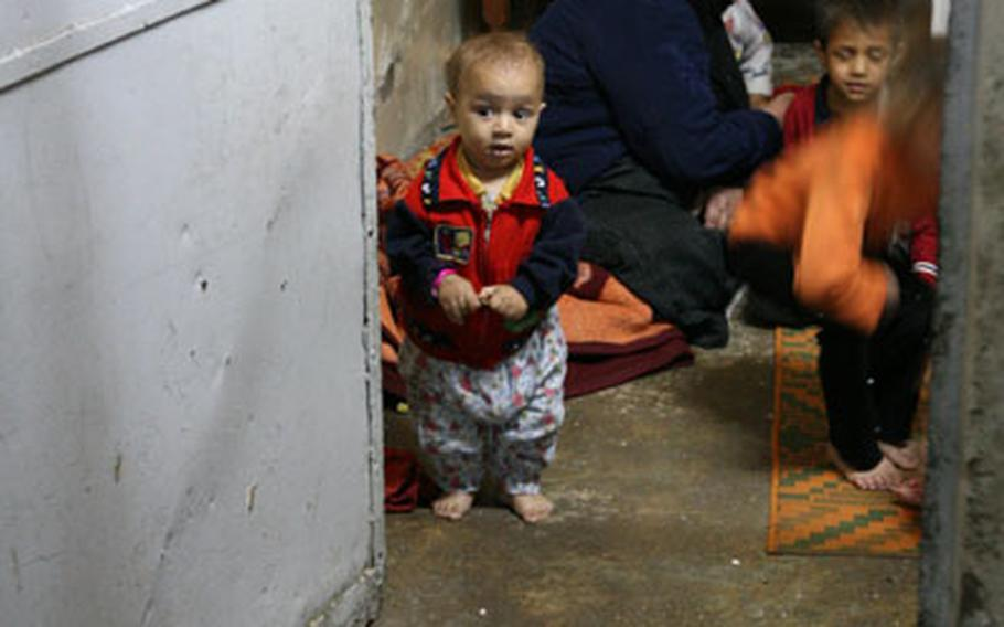 An Iraqi boy looks out of a room at U.S. troops during a raid. The raid, by Company A, 2nd Battalion, 7th Cavalry Regiment targeted suspects in a bombing that killed two U.S. soldiers the previous morning on Halloween.