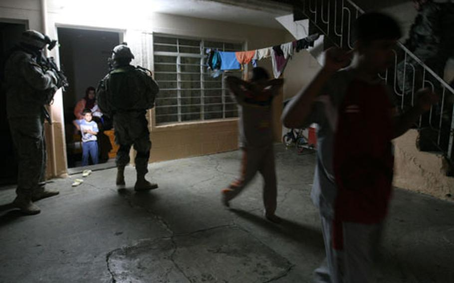 U.S. troops order Iraqi civilians out of a room during a raid. The suspected trigger man was not found, but another suspect was. Two others have since been detained.