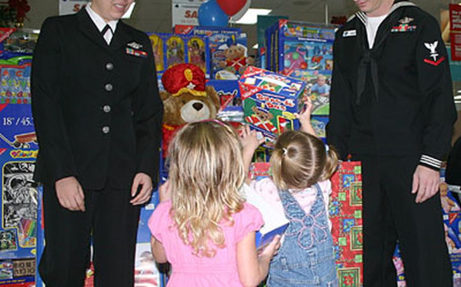 Hannah Silva, right, 3, and her sister Hailey, 2, donate some of the first toys to the Marine Corps Reserve Toys for Tots campaign on Okinawa after the opening ceremony at the Camp Foster main exchange. Petty Officers 3rd Class Nina Kovacs and Christopher Colley volunteered to be the first to man the donation boxes.