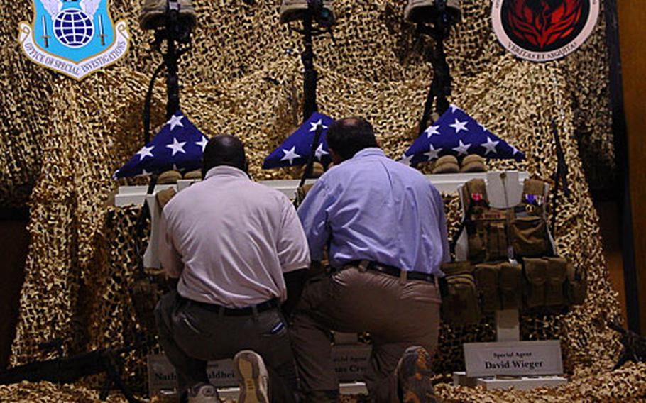 Two unidentified members of an Air Force Office of Special Investigations team on Sunday honor three special agents who died from a roadside bomb last Thursday near Balad Air Base in Iraq.