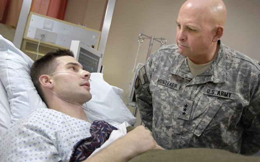 Lt. Gen. Kenneth Hunzeker, commander of V Corps, visits with Sgt. Kenneth Towne, a Marine from the 2nd Intelligence Battalion out of Camp Lejeune, at Landstuhl Regional Medical Center. Hunzeker, who has made numerous visits to the hospital, said during this visit that the attitude of the wounded warriors here always picks up his morale. Towne was sent to LRMC from Iraq after complications occurred from an appendectomy.