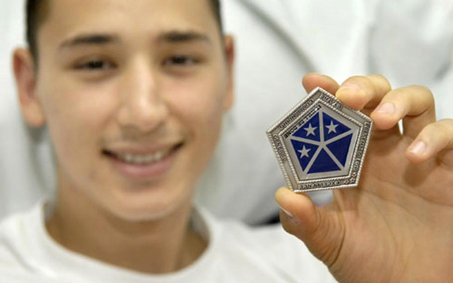Army Spc. Sean Staggs shows off his V Corps coin presented by Lt. Gen. Kenneth Hunzeker, commander of V Corps.
