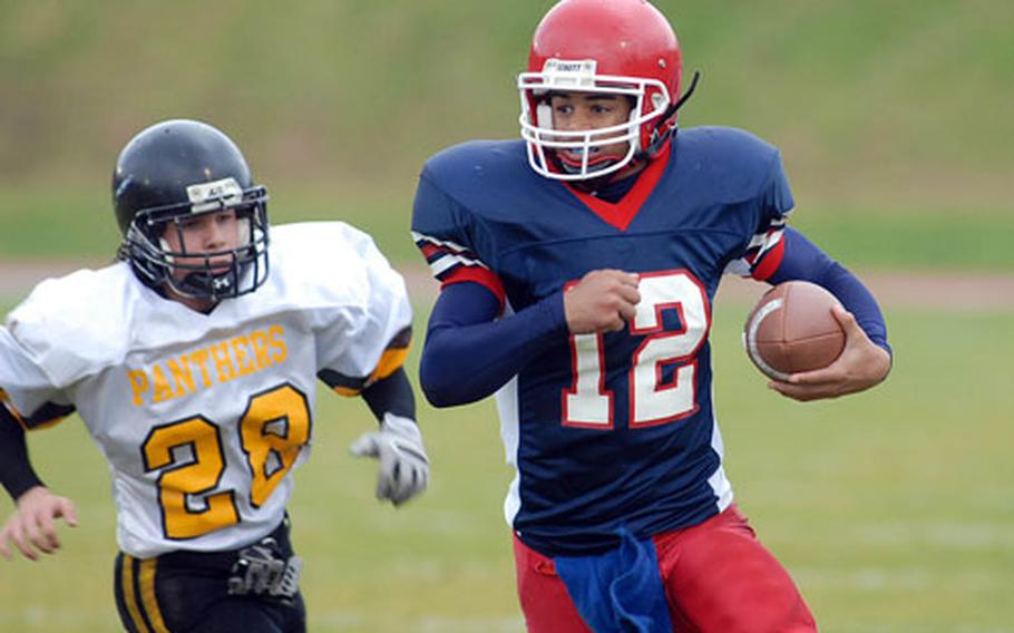 Mustang quarterback Scottie Setzer sprints away from Hanau's Kevin Perdue, in Menwith Hill's Division IV title game loss against the Panthers.