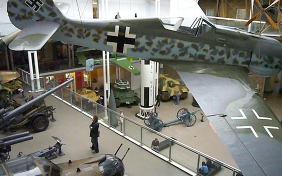 A German Focke-Wulf Fw 190 fighter hovers from the ceiling above other military pieces inside London's Imperial War Museum.