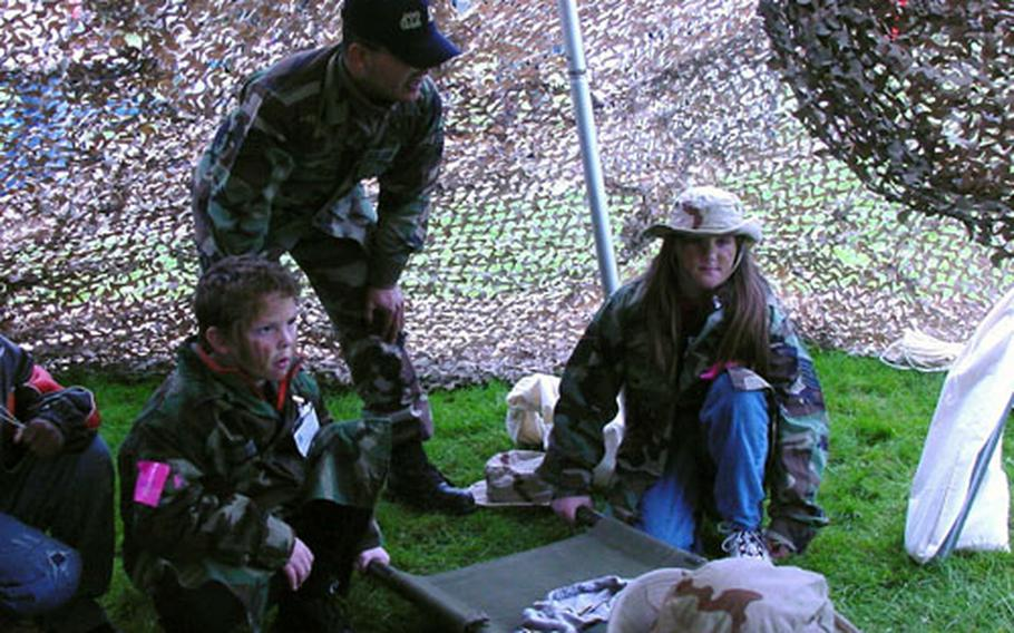 Under the guidance of Staff Sgt. Christian Aguilar, fourth-graders Aulden Walling, left, and Hayley Presciti receive instruction on the correct way to evacuate a patient using a stretcher.