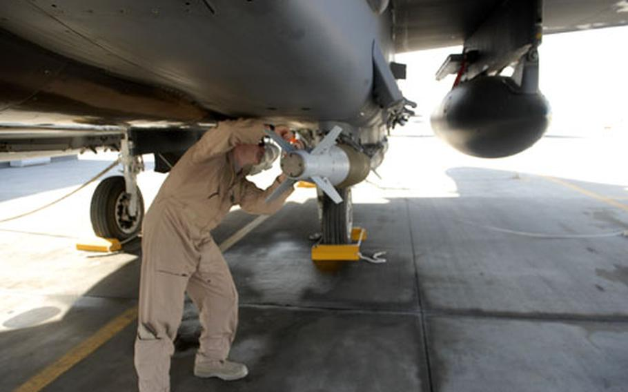 U.S. Air Force Capt. Tom Veilleux, 27, of Attleboro, Mass., goes over an F-15 attack aircraft at Bagram Air Field in Afghanistan.