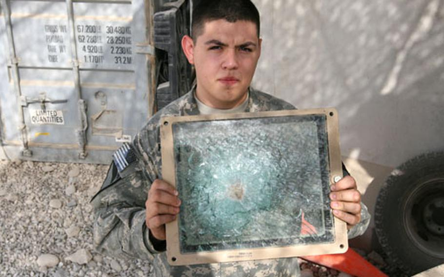 Spc. Gabriel Hernandez, 22, of San Antonio displays a bulletproof face shield that took a direct hit recently from a 7.62mm round fired by insurgents. The shield saved the gunner from being hit in the face.