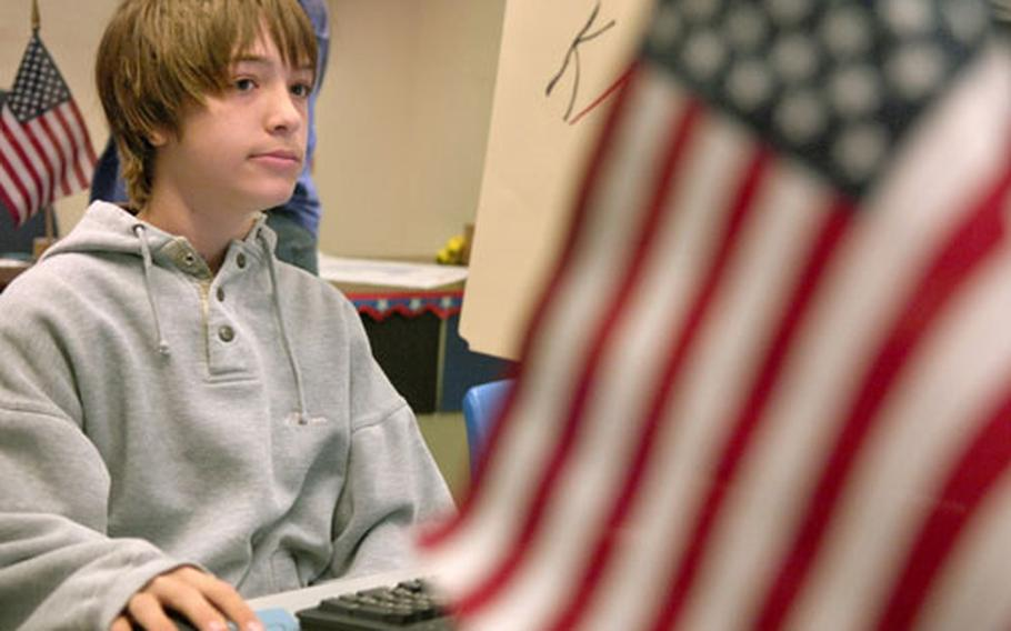 Andre Buchanan-Dempsey, an eighth-grader at Kaiserslautern Middle School in Germany, casts his vote.