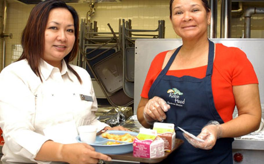 School Lunch Program Coordinator Ellen Sapnit, left, and Food Server Lorette Santos display one of the lunches prepared for Nile C. Kinnick High School students Tuesday.