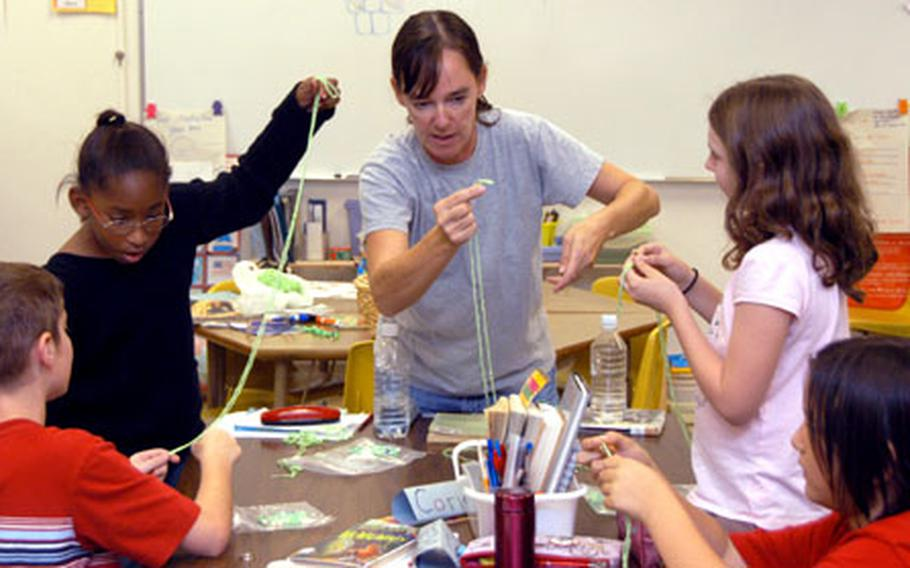 Beverley Rivera instructs fourth-graders Tuesday at Kadena Air Base, Okinawa, on how to make a snake out of yarn and beads. Rivera, a Kadena Elementary School parent, was in class teaching as part of American Education Week.