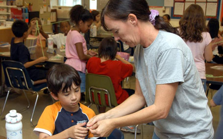 Beverley Rivera shows fourth-grader Colby Harter how to string beads to make a snake Tuesday during a craft project at Kadena Air Base, Okinawa.