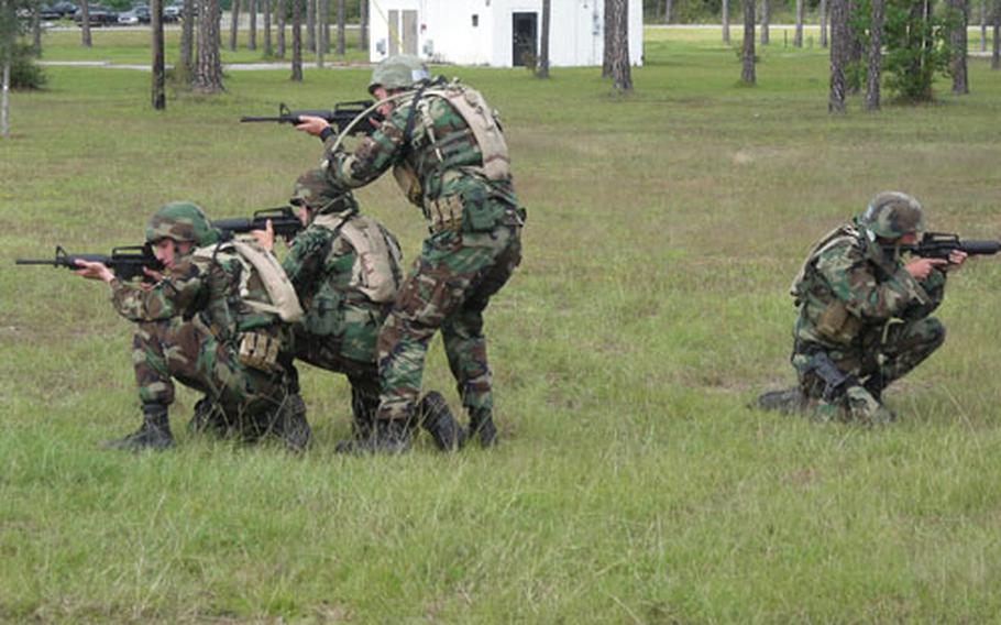 Expeditionary Combat Skills students assume fighting positions while conducting bailout training with Humvees.