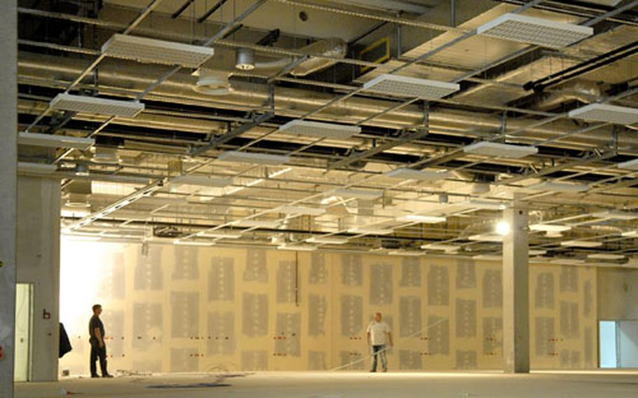 Construction workers lay cabling in the future electronics section of the Power Zone in the Kaiserslautern Military Community Center.
