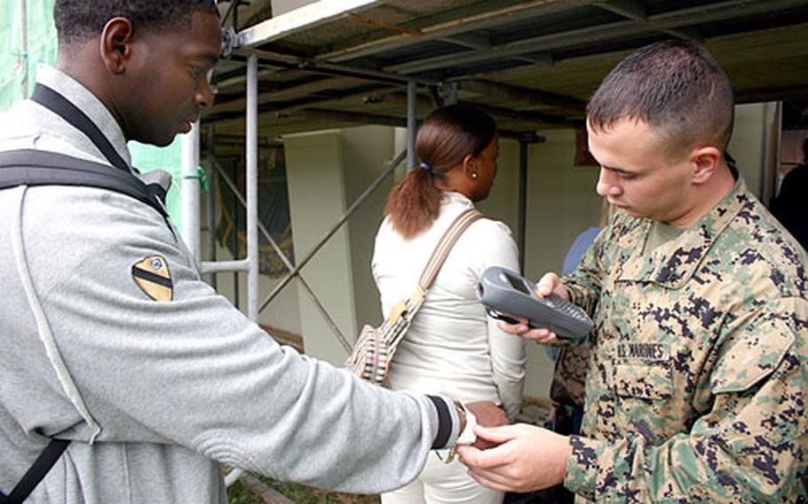 Lance Cpl. Ryan Jacobs, right, with Marine Aerial Refueler Transport Squadron, scans wrist bands Wednesday morning during a noncombatant evacuation operation exercise so that the tracking systeM can record their new location on Marine Corps Air Station Futenma.