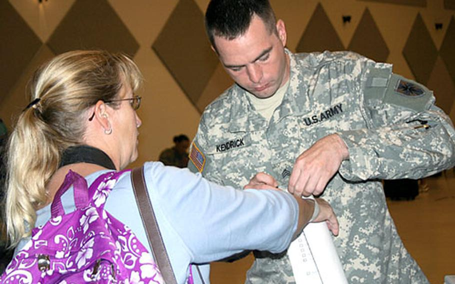 Army Sgt. Rodney Kendrick attaches a bar-code band around the wrist of Melanie O'Neill, an Army spouse. The bar code was entered into a tracking system along with O'Neill's personal information, and at several checkpoints throughout the evacuation process it was scanned so that O'Neill's location could be tracked.