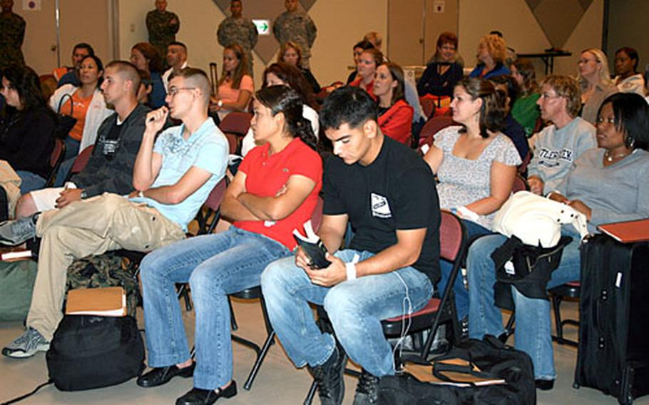 """""""Evacuees,"""" servicemembers and family members who volunteered, listen to a briefing at the Camp Foster, Okinawa, Community Center on Wednesday morning during a noncombatant evacuation operation exercise."""