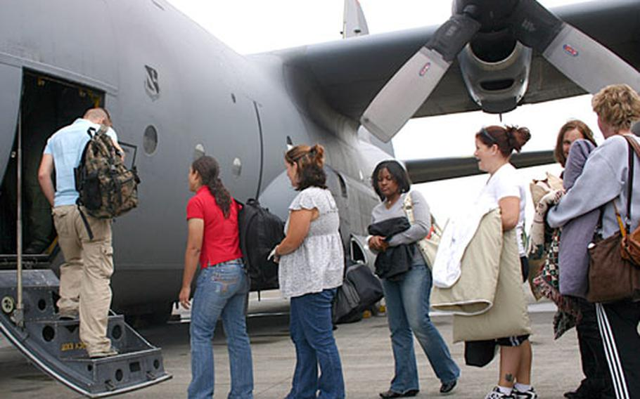 Volunteers board a C-130 at Marine Corps Air Station Futenma, Okinawa, bound for a Japanese base in Miho as part of a noncombatant evacuation operation exercise which started on Camp Foster, Okinawa, early Wednesday morning.