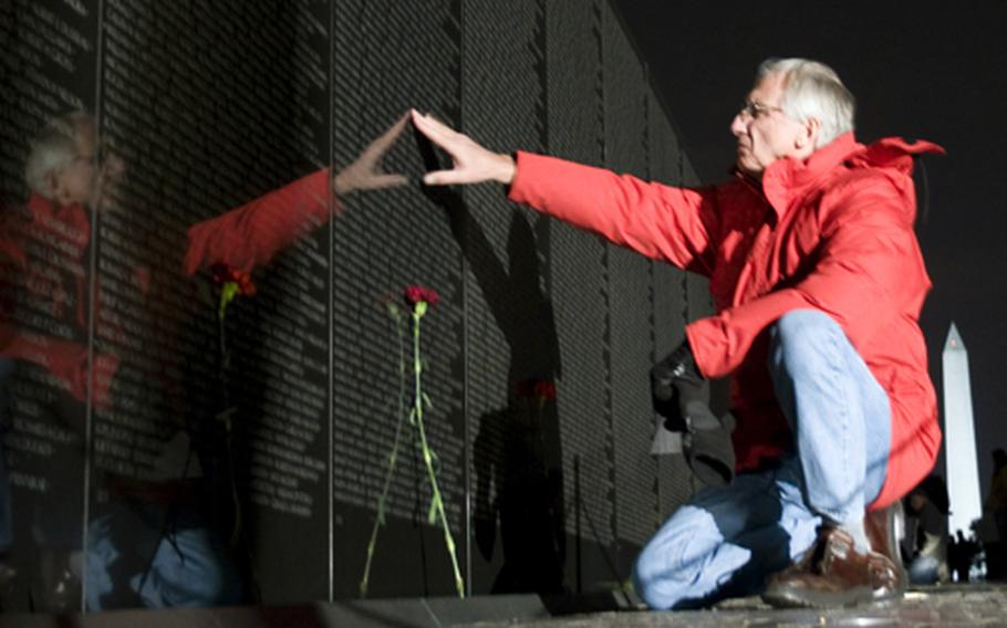 John Lazarczyk pauses at the panel bearing the name of James D. Williamson Thursday night at the Vietnam Veterans Memorial in Washington, D.C.