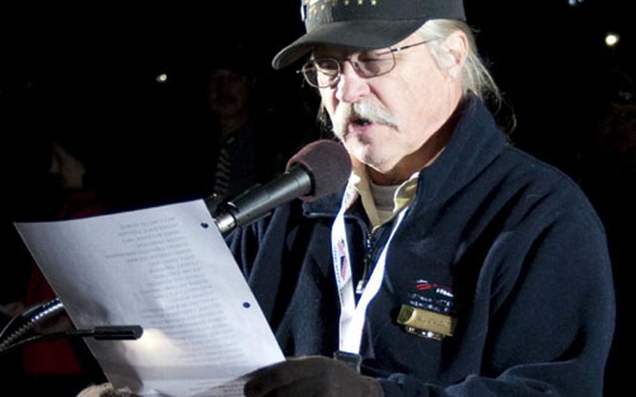 Vietnam veteran Paul Stancliff reads names at the Vietnam Veterans Memorial Thursday night.