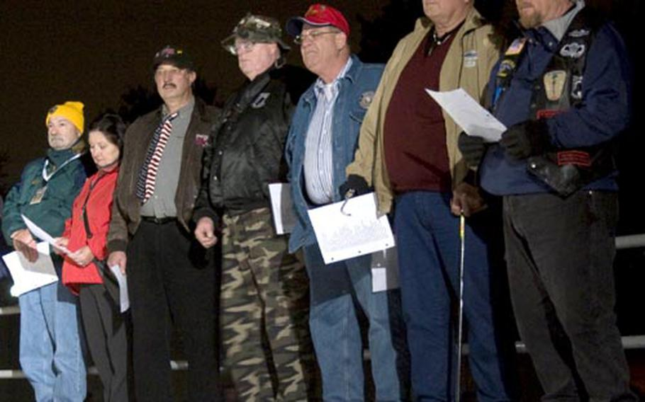 Veterans and other volunteers wait their turn to readc names Thursday night.