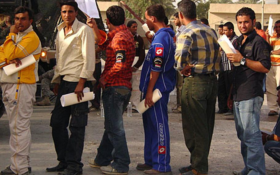 """Iraqi police recruits stand in line during an all-day screening. Coalition forces are trying to help Iraq's Ministry of Interior hire thousands of new police for Baghdad in hopes of putting many of them in place before the U.S. military """"surge"""" in forces leave early next year."""