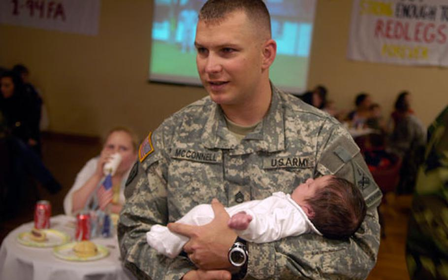 Staff Sgt. Erik McConnell, who returned home just a few days ago form his training deployment, holds newborn son Zon. In all, 10 babies were delivered by 1-94 spouses during the three-month deployment.