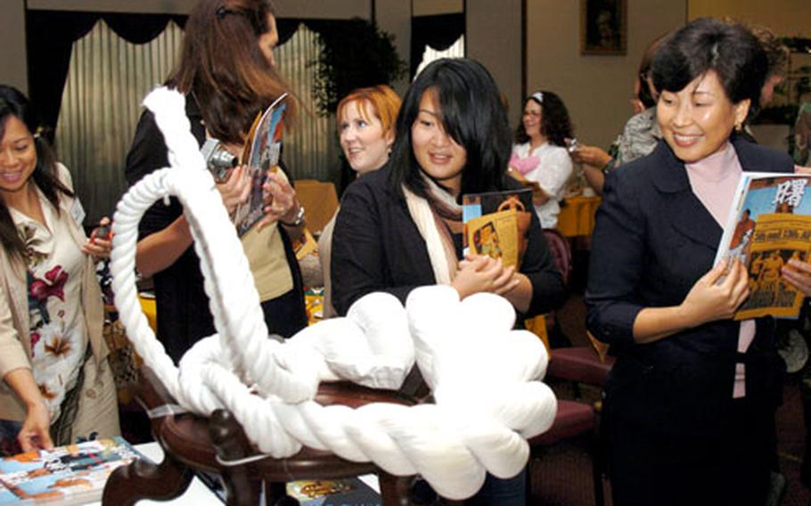 Yokota Officers Spouses Club members check out the tsuna, an ornamental piece worn by Chad Rowan, better known as Akebono, in his tournaments.