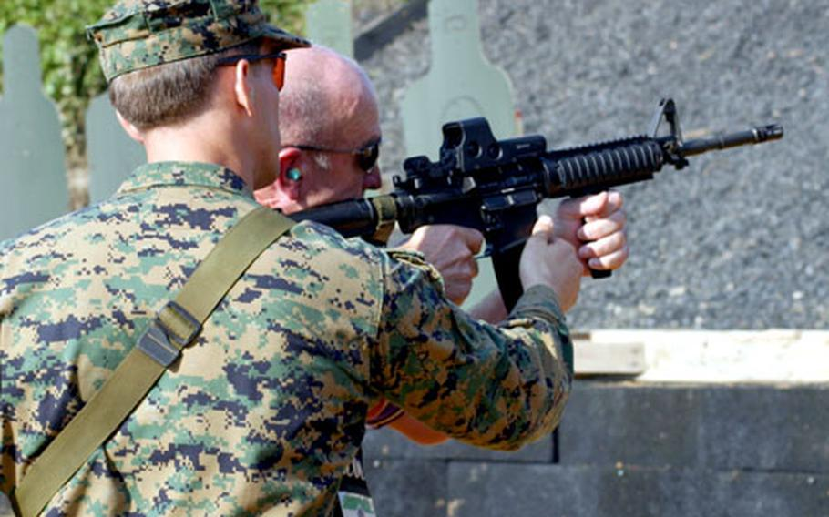 Staff Sgt. Mark Castille, with the Special Operations Group, helps Carl Cramer, president and owner of Ferell's Health Centers in Bremerton Wash., correct his aim with the M16A2 during a live-fire exercise Saturday for the Joint Civilian Orientation Conference's visit to Camp Hansen.