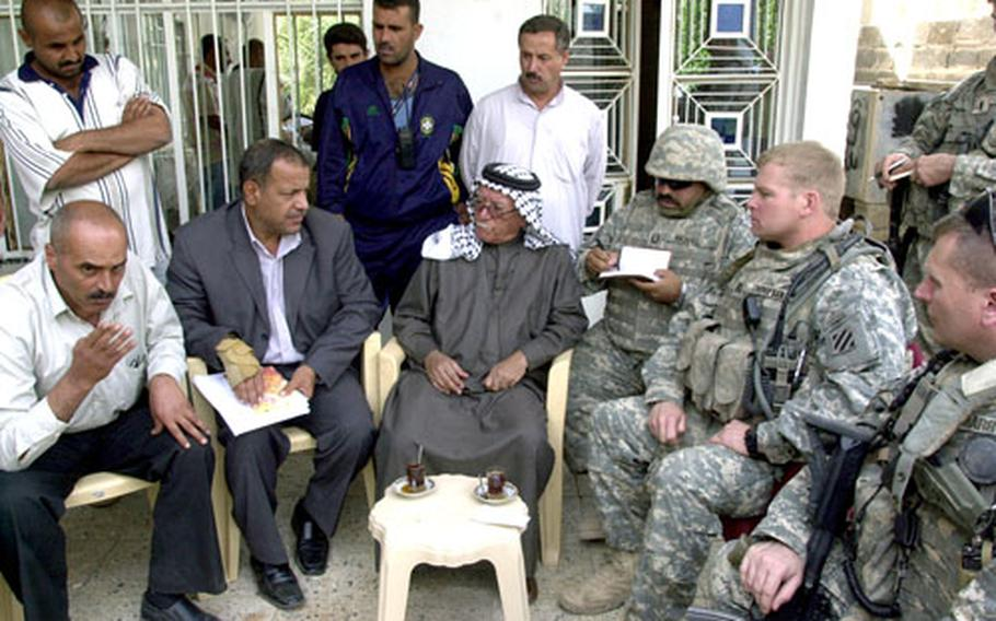 """Sheiks and """"concerned citizens"""" speak with soldiers from the 3rd Infantry Division's 1st Battalion, 15th Infantry Regiment at a neighborhood meeting Thursday in Al-Jara, a village about 20 miles southeast of Baghdad. Soldiers say that Sheik Nori Zbar Al-Jaboori, center, has helped lead hundreds of predominantly Sunni citizens to work with mostly Shiite police to drastically curb insurgent attacks."""