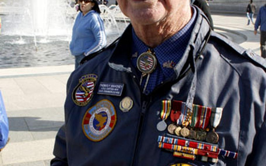 Pearl Harbor survivor Thomas F. Mahoney displays some shrapnel from the attack during a Veterans Day visit to the memorial. Mahoney served on the USS O'Bannon, which received 17 battle stars — more than any other destroyer in World War II.