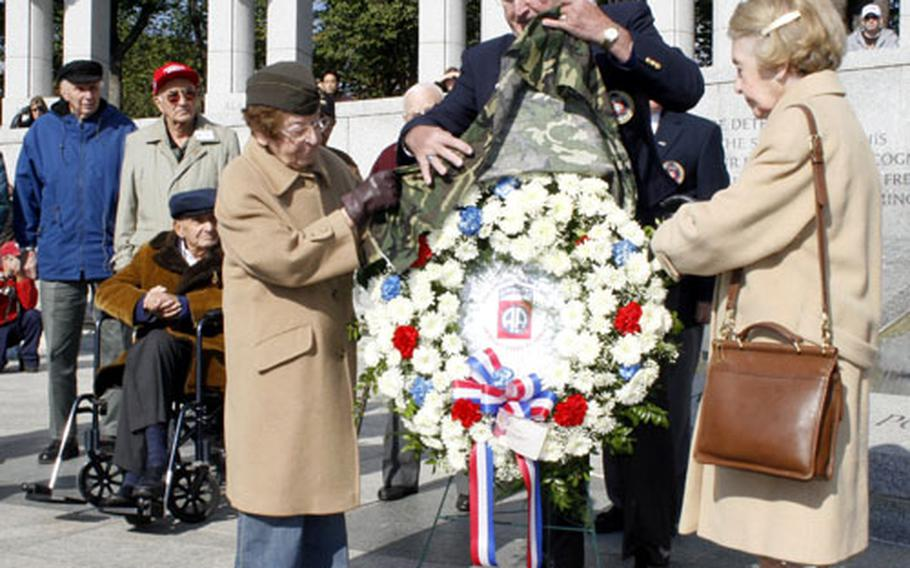 Ellan Orkin, left, and Dorothy Sinner help unveil a wreath during Veterans Day ceremonies Sunday at the National World War II Memorial. The two sisters served as nurses with the 164th General Hospital in Normandy in 1944 and 1945.