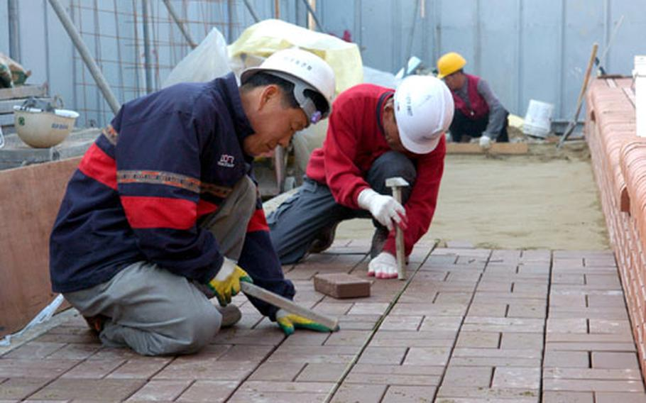 At Camp Humphreys in South Korea, workers lay a brick walkway during construction of a community pavilion just inside the post's walk-in gate.