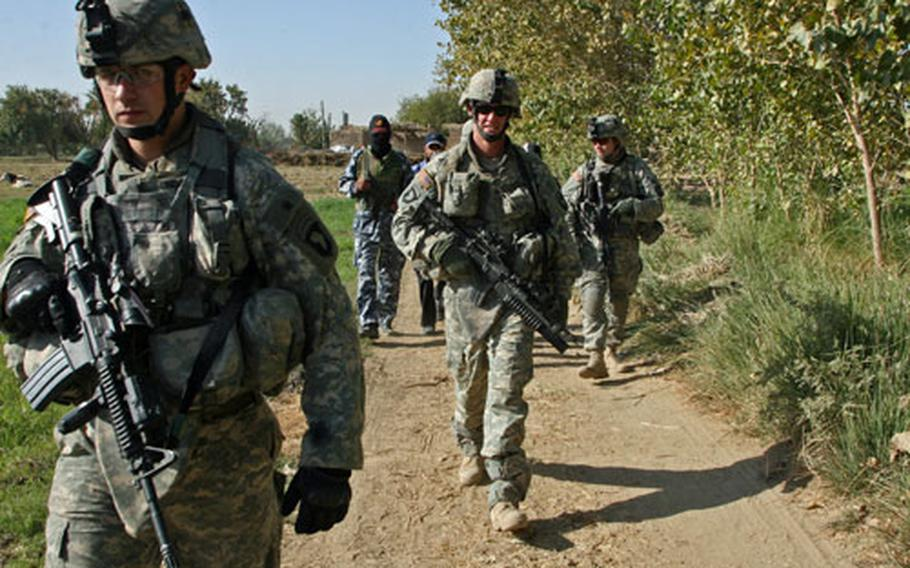 """Soldiers with Co. A, 1st Battalion, 327th Infantry Regiment move out during a patrol near Beiji, Iraq. The soldiers were conducting a """"sphere of influence"""" mission, during which they met with local residents to hear their concerns and assure them that they could rely on U.S. and Iraq forces for protection against insurgents."""