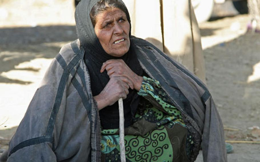 An old Bedouin woman watches as Pvt. 1st Class John DeLoach, of Co. A, 1st Battalion, 327th Infantry Regiment, 101st Airborne Division, treats burns on her granddaughter's legs and backside during a patrol near Beiji, Iraq.