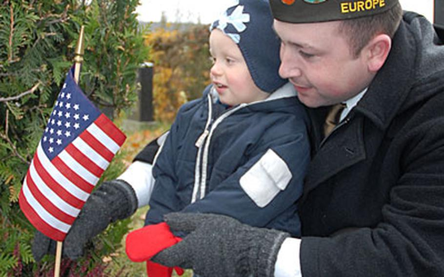 In honor of Veterans Day, Travis Fosmo, a member of Veterans of Foreign Wars of the United States Richard E. Austin Post 10592, and his son Fabian, 2, replace a flag at the grave of an American serviceman at a cemetery in downtown Bamberg, Germany.