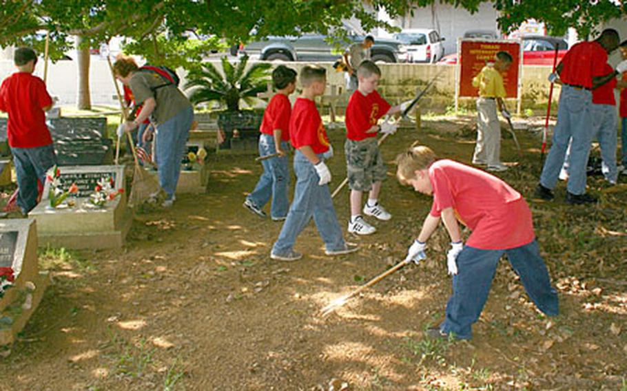 The Camp Foster Young Marines, with some help from their parents and Marines who volunteer with the program, mow grass, rake leaves and clear the headstones at the Tomari International Cemetery in Naha on Sunday.