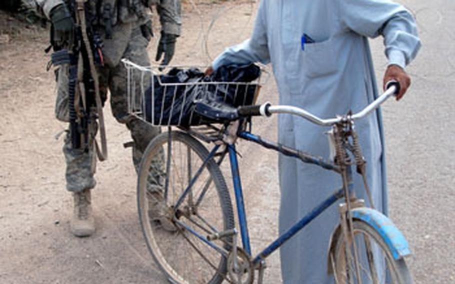 Spc. Noel Gaulard, 22, of Bryan, Ohio, searches a cyclist near Combat Outpost Aztec on Monday.