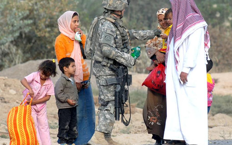 Spc. Craig Luther, 21, of Vermilion, Ohio hands sweets to Iraqi children near Combat Outpost Aztec on Monday. Luther is part of Company D, 2nd Squadron, 2nd Stryker Cavalry Regiment.