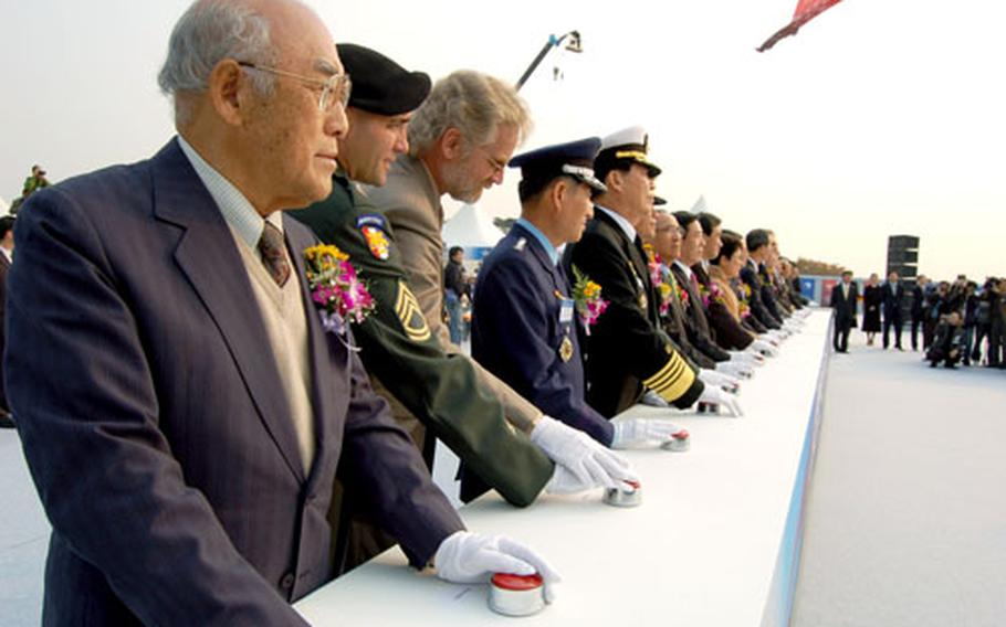 South Korean dignitaries and officials from U.S. Forces Korea prepare to push buttons to send colorful columns of smoke into the air Tuesday.