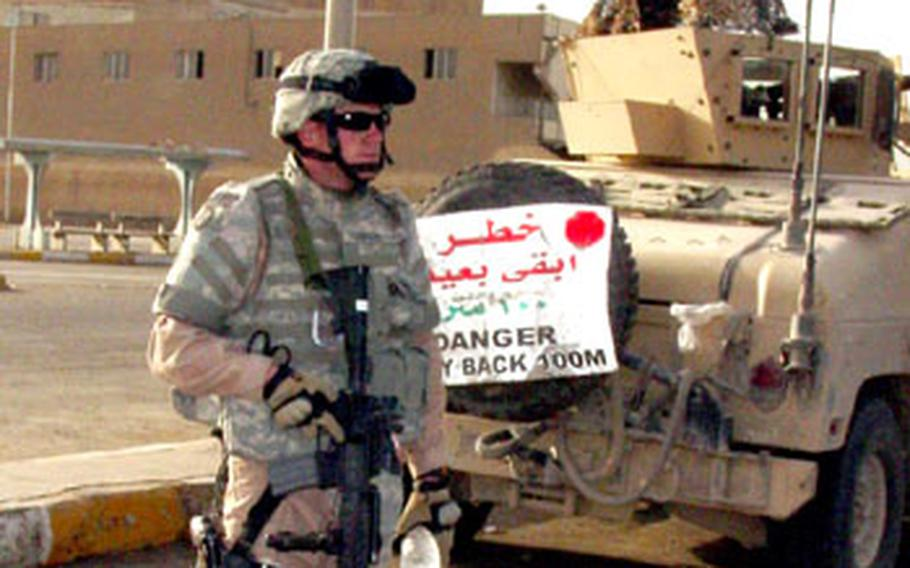 """Air Force Staff Sgt. Travis Griffin from the 732nd Expeditionary Security Forces Squadron's Detachment 3 guards a Humvee at Baghdad's main bus station on Thursday. While most airmen serving in Iraq rarely venture outside the base, members of Detachment 3 go almost every day as part of the service's effort to fill jobs that have typically been done by the Army in Iraq. The Air Force calls them """"in lieu of"""" taskings."""