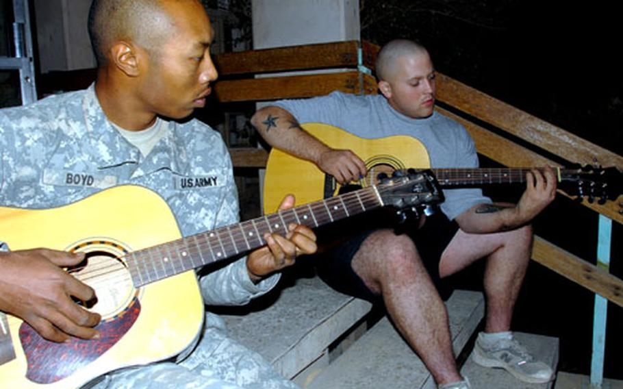 Spc. Gary Boyd, 24, of Morrow, Ga., left, and Pfc. Ivy Harris, 21, of Adairsville, Ga. play guitar on the front steps at Combat Outpost Aztec, Baghdad, Iraq on Tuesday.