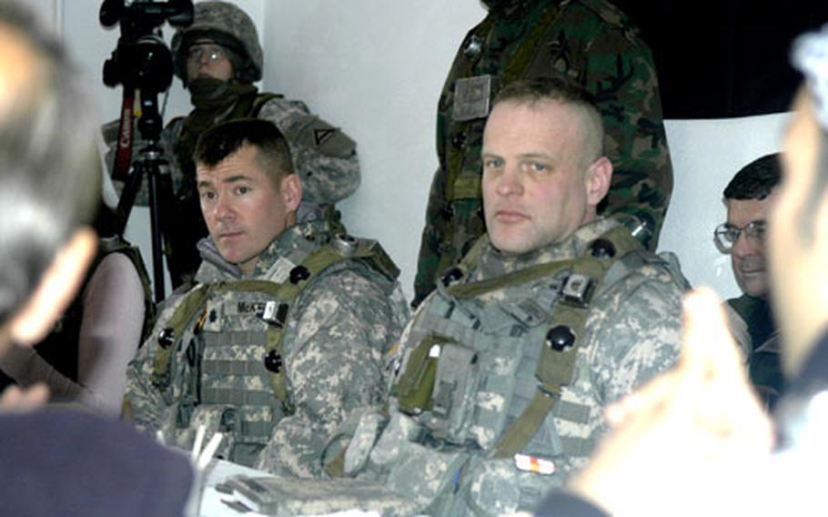 Lt. Col. Matthew McKenna, left, and Lt. Col. Michael Shrout of the 2nd Brigade, 1st Armored Division, listen to Iraqi provincial government and tribal leaders during a training exercise in Hohenfels, Germany. The actors are prohibited from being photographed, in part, because some still have ties to the Iraq region. Monitors from the Joint Multinational Readiness Center observe and later critique the performance of the commanders and soldiers in the exercise.