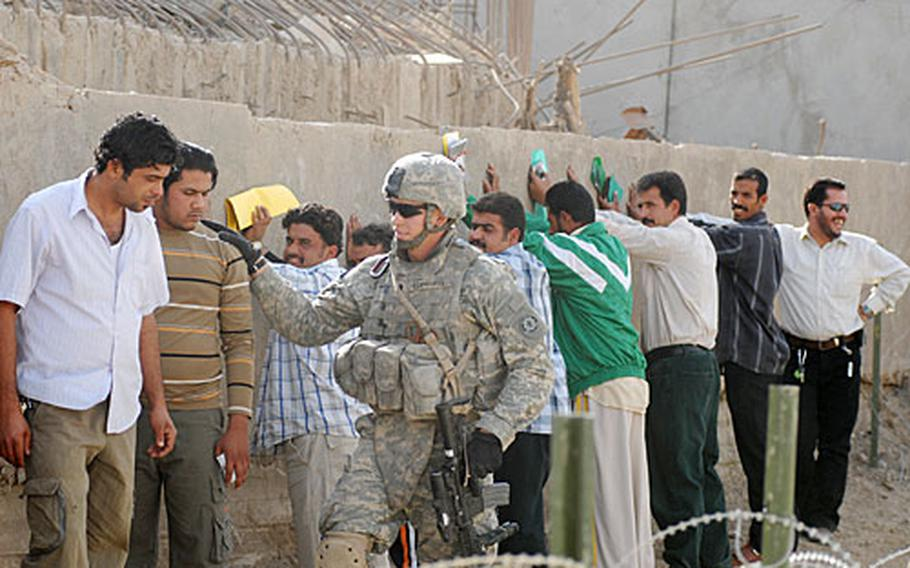 Sunnis applying for Iraqi security forces jobs are searched by a 2nd Cavalry (Stryker) Regiment soldier after they arrived at Joint Security Station Cougar.