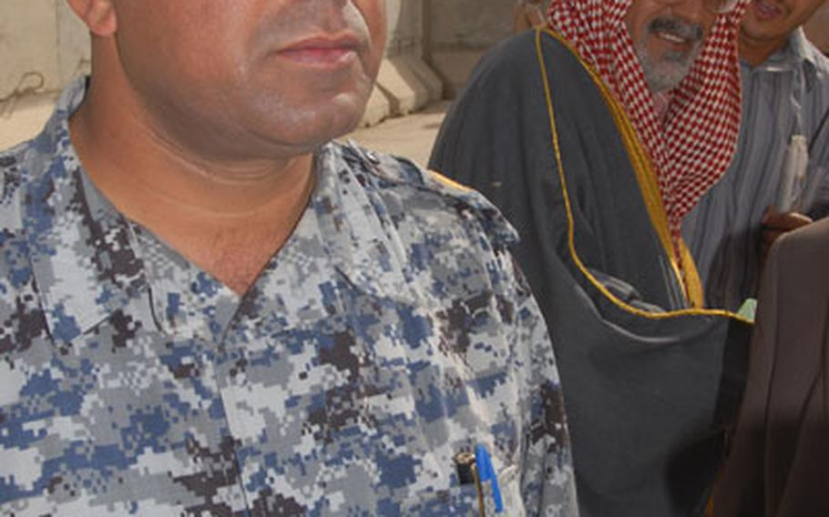 From left: Lt. Col. Fakhir Idair Al Bahadpy, a Shiite, who heads a 400-man battalion of Iraqi Police, and Fasul Abued Hasson Al Joburi, a Sunni sheik, who lead about 100 members of his clan onto Joint Security Station Cougar to apply for security forces jobs.