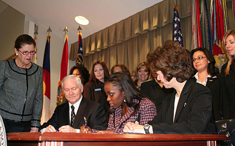 Defense Secretary Robert Gates, left, and Labor Secretary Elaine Chao watch as Gwen Bates, whose husband is a Navy petty officer, co-signs a proclamation funding a new $35.2 million Military Spouse Career Advancement Initiative at the Pentagon.