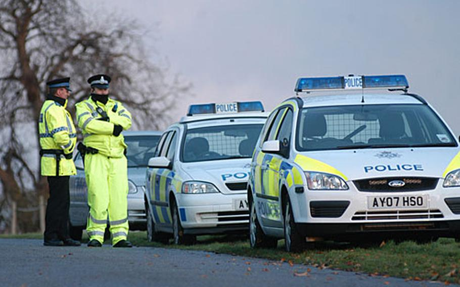 British police officers guard the entrance to a Redgrave poultry farm where birds tested positive for the deadly H5N1 avian influenza virus. Medical facilities at RAF Lakenheath, located less than 30 miles from the farm, say they stand ready if the outbreak worsens.