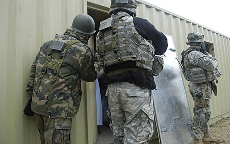 Soldiers clear a building to locate suspects and collect information during a mission rehearsal exercise in Hohenfels, Germany. The soldiers work to perform the difficult balancing act of achieving security and not upsetting peaceful civilians.