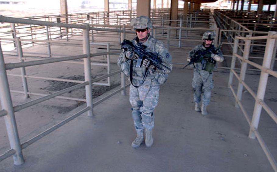Company D, 2nd Squadron, 2nd Cavalry (Stryker) Regiment soldiers Sgt. Jacob Rogers, 27, of Ennis, Texas (left) and Spc. Shawn Derrick, 21, of Wenatchee, Wash. patrol through stockyards at what used to be Iraq's largest meat-works on Wednesday.